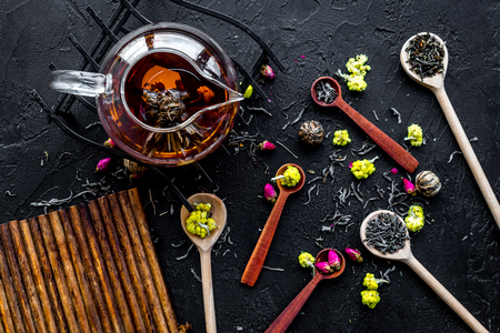Brew the aromatic tea. Tea pot near wooden spoons with dried tea leaves, flowers and spices on black wooden background top view.