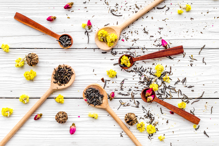 Aromatic tea. Wooden spoons with dried tea leaves, flowers and spices on white wooden background top view.