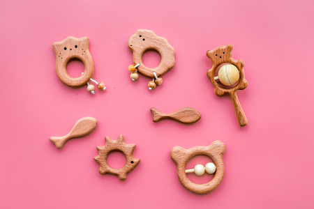 Simple handmade toys for newborn baby in shape of animals on pink background top view.