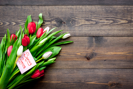 First spring flowers. Bouquet of colorful tulips near Spring is coming note on dark wooden background top view copy space
