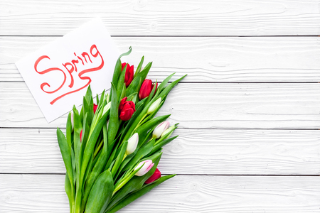 Waiting for spring. Spring lettering near bouqet of tulips on white wooden background top view copy space