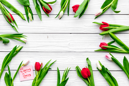 Waiting for spring. Spring is coming lettering near tulips and macarons on white wooden background top view space for text