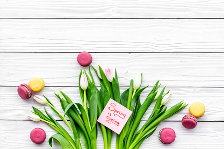 Waiting for spring. Spring is coming lettering near bouqet of tulips and macarons on white wooden background top view space for text Stock Photo
