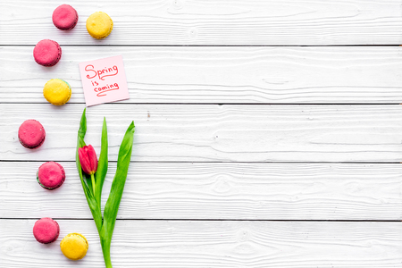 Waiting for spring. Spring is coming lettering near bouqet of red tulips and macarons on white wooden background top view space for text Stock Photo
