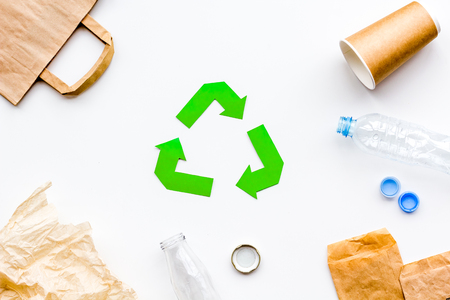 Sorting waste and recycle. Green paper recycling sign among waste paper, plastic, glass, polyethylene on white background top view Foto de archivo