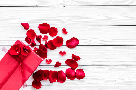 Gift for Valentines day. Red gift box near red rose petals on white wooden background top view copy space Stock Photo