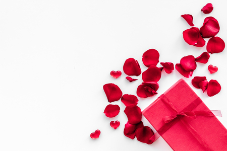 Gift for Valentines day. Red gift box near red rose petals on white background top view.