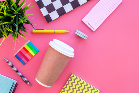 Students desk. Notebook, stationery, coffee cup on pink background top view copy space
