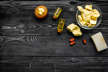 Cocoa butter as ingredient for natural cosmetics. Dark wooden background top view. Stock Photo