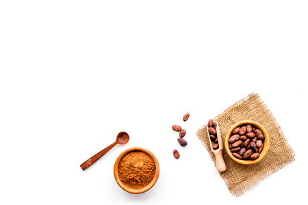 Main ingredient for chocolate. Cocoa powder in bowl near cocoa beans on white background top view.