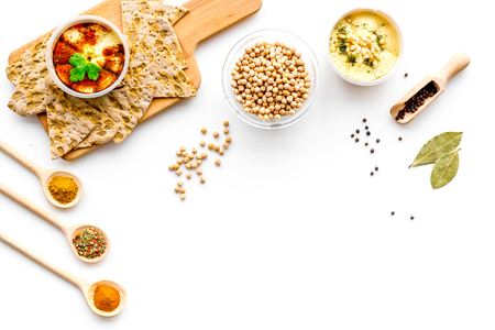 Middle Eastern cuisine. Bowl with hummus among pieces of crispbread and spices on white background top view. Stock Photo