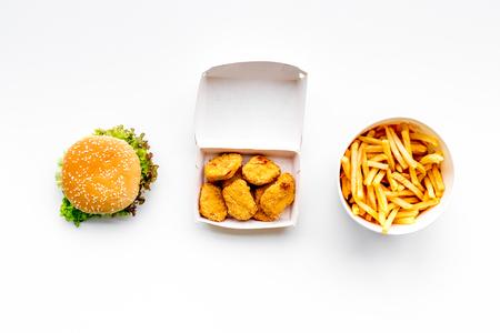 ファーストフード。白い背景のトップビューにチケンナゲット、ハンバーガー、フライドポテト。
