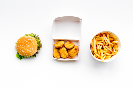Fast food. Chiken nuggets, burgers and french fries on white background top view. Imagens