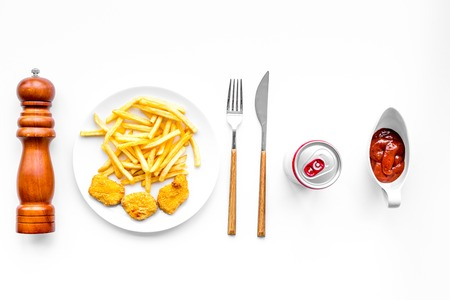 Fast food reastaurant. Chiken nuggets and french fries on plate on white background top view Stock Photo