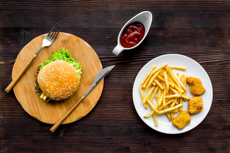 Most popular fast food meal. Chiken nuggets, burgers and french fries on dark wooden background top view.