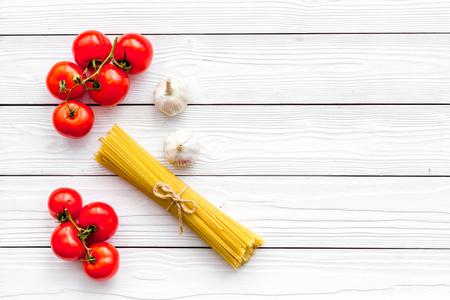 Voorbereiding om pasta te koken. Spaghetti, tomaten, knoflook, lepel voor spaghetti op de witte houten mening van de lijstbovenkant. Stockfoto