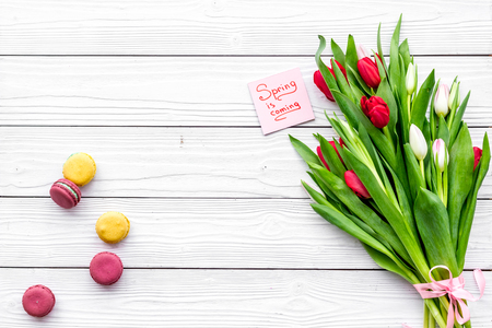 Waiting for spring. Spring is coming lettering near bouqet of tulips and macarons on white wooden background top view.