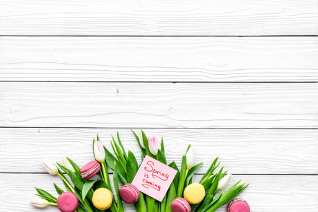 Waiting for spring. Spring is coming lettering near bouqet of tulips and macarons on white wooden background top view. Banco de Imagens - 94340198