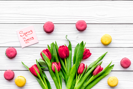 Waiting for spring. Spring is coming lettering near bouqet of red tulips and macarons on white wooden background top view.