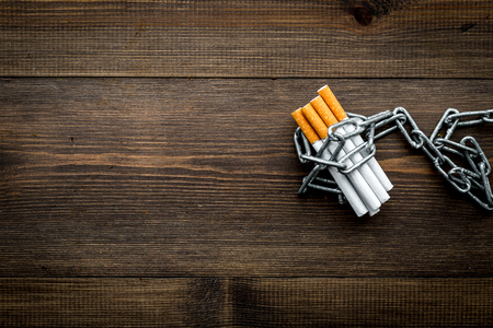 Quit smoking. Cigarettes in chains on dark wooden background top view. Stock Photo - 94340213
