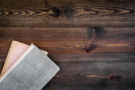 読書と自己啓発。暗い木製の背景トップビュー上の古い本。 写真素材