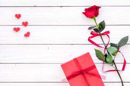 Prepare the prsesnts or surprise for Valentines day. Red gift box near red rose on white wooden background top view.