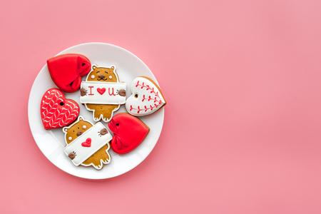 Snoepjes op Valentijnsdag. Koekjes in de vorm van hart en met letters ik hou van je op roze achtergrond bovenaanzicht.