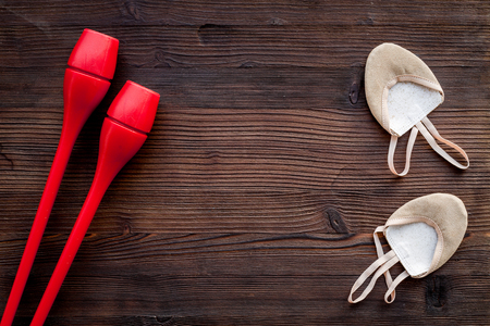 Equipment for rhythmic gymnastics. Clubs and gymnastics shoes on dark wooden background top view. Imagens