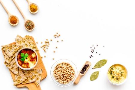 Cucina mediorientale. Lanci con il hummus fra i pezzi di pane croccante e le spezie sulla vista superiore del fondo bianco. Archivio Fotografico - 94320556