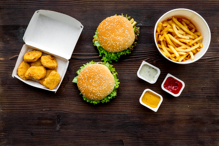 Most popular fast food meal. Chiken nuggets, burgers and french fries on dark wooden background top view copy space