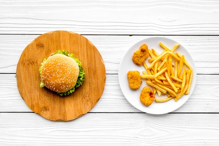 Most popular fast food meal. Chiken nuggets, burgers and french fries on white wooden background top view Stock Photo