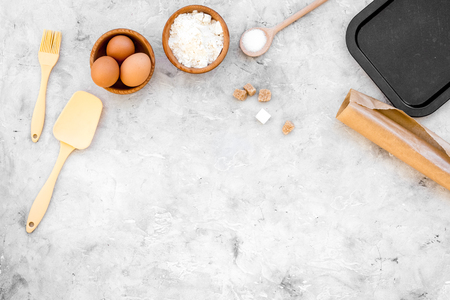 Make dough. Ingedients flour, eggs near cookware on grey background top view. Stock Photo