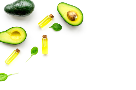 Natural products for skin care. Avocado oil in bottles near sliced avocado on white background top view copy space