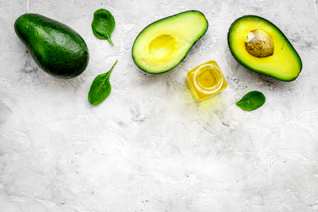 Natural products for skin care. Avocado oil in bottles near sliced avocado on grey background top view. Stok Fotoğraf
