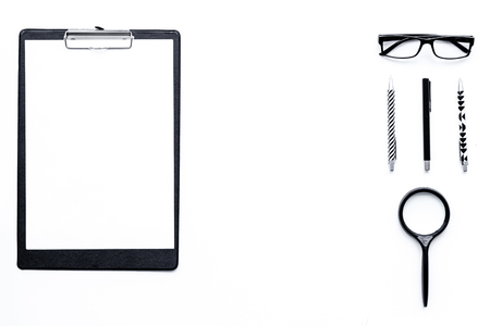Strict monochrome office desk table with pad, stationery, magnifying glass, glasses on white background top view.