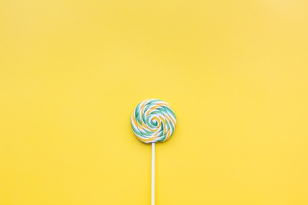 Colorful lollipop swirl on yellow pastel background top view. Stock Photo