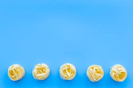 Uncooked tagliatelle. Italian pasta. Pattern on pastel blue background top view copy space