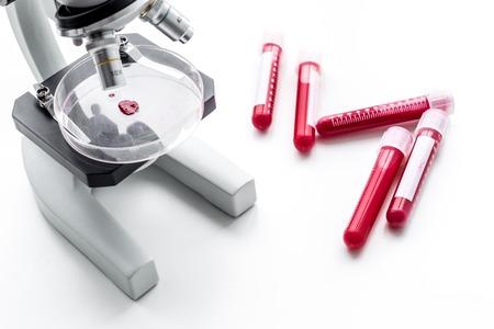 Bloedonderzoek concept. Bloedmonsters dichtbij microscoop op witte hoogste mening als achtergrond. Stockfoto