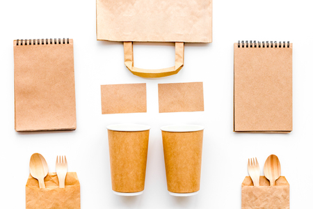 Disposable tableware. Paper cup, spoon, fork near brown paper bag and notebook top view mock up.