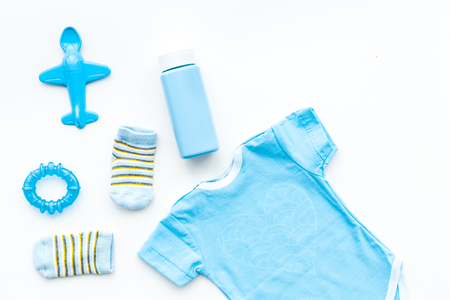 Blue set for newborn boy. Baby bodysuit, socks, airplan toy and powder on white background top view. Banco de Imagens