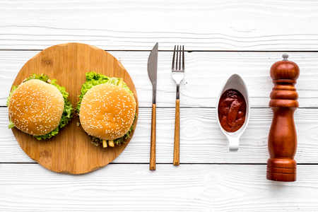 Burger on wooden cutting board on white wooden background top view. Foto de archivo