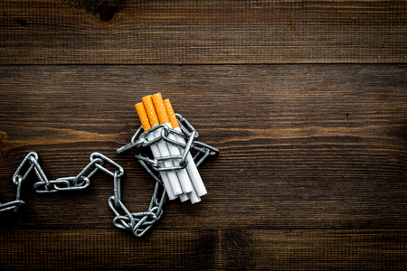 Quit smoking. Cigarettes in chains on dark wooden background top view copy space Stock Photo - 94610782
