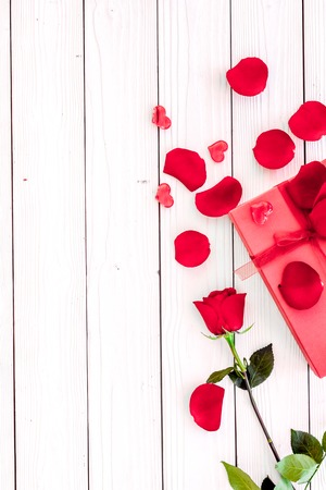 Prepare the prsesnts or surprise for Valentines day. Red gift box near red rose and petals on white wooden background top view space for text