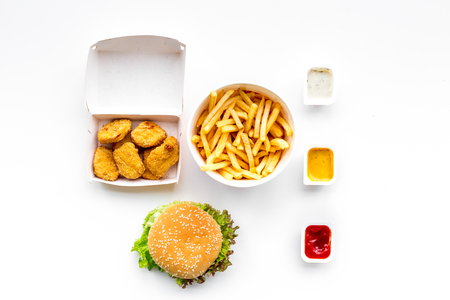 Fast food. Chiken nuggets, burgers and french fries on white background top view Stockfoto
