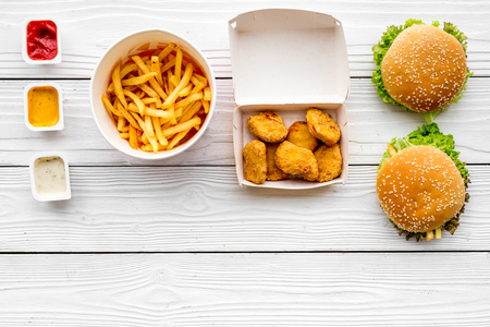 Most popular fast food meal. Chiken nuggets, burgers and french fries on white wooden background top view copy space Stock Photo