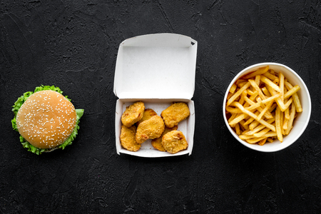Most popular fast food meal. Chiken nuggets, burgers and french fries on black background top view Stock Photo
