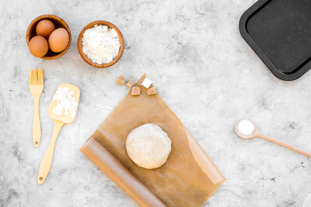 Make dough. Ingedients flour, eggs near cookware on grey background top view