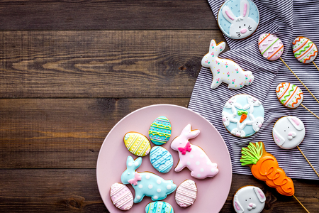 Easter bunny and easter eggs cookies. Sweets, pastry for Easter table. Dark wooden background top view.