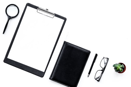 Strict work desk with pad, glasses, magnifiger, notebook, plant on white background top view copy space mock up