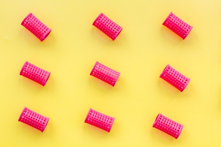 Red curlers for hairdress. Pattern on yellow pastel background top view